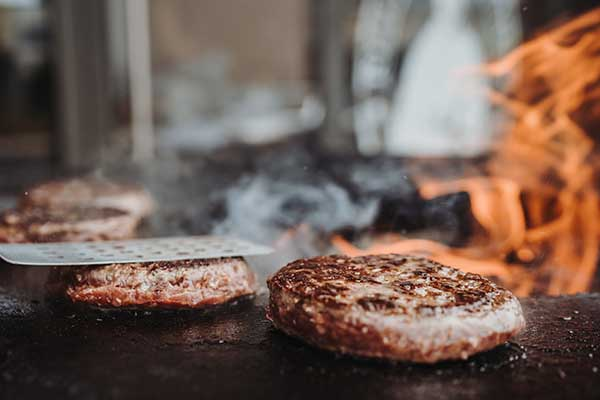Die Patties auf dem Grill oder der Plancha grillen