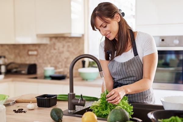 Eine Frau wäscht an einem Becken einen Salat - Küchenhygiene