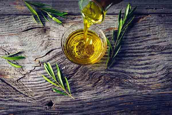 Olivenoel wird in ein Glas gegossen