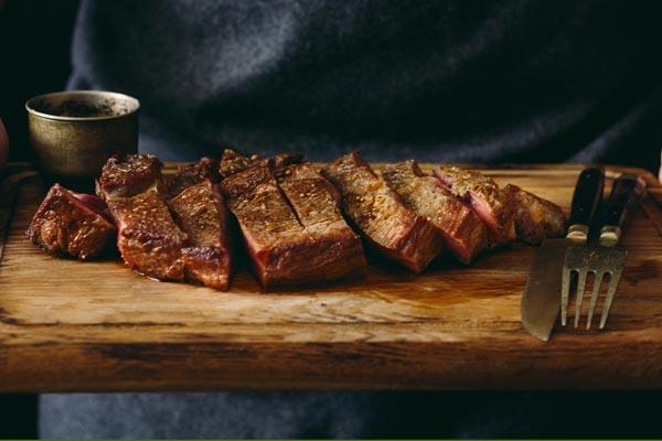 Zubereitetes Steak auf Holzbrett mit Besteck