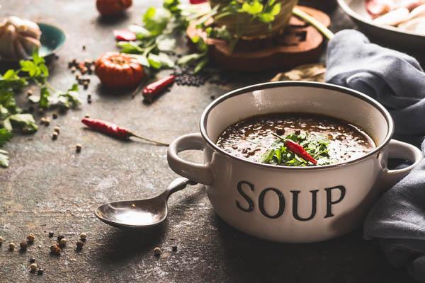 Suppentasse auf rustikalem tisch mit Kräutern und Gewürzen